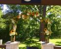 This archway at The Springs in Rockwall, Texas was designed with large sunflowers, white hydrangeas, green hanging amaranthus & several mixed greens.