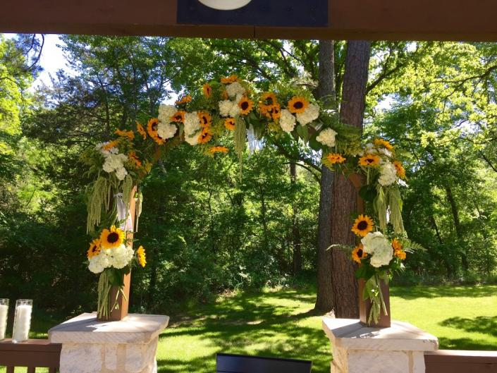 This archway at The Springs in Rockwall, Texas was designed with large sunflowers, white hydrangeas, green hanging amaranthus & several mixed greens.]