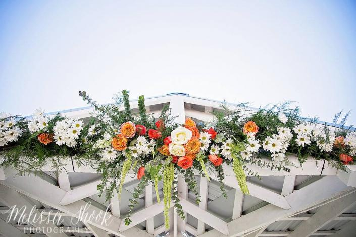 [Image: This 9 foot archway was designed with many mixed greens, dark orange roses, coral roses, white roses, white daisies & hanging green amaranthus.]