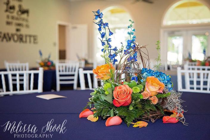 "[Image: The them for this wedding was ""Love Birds"". It was designed in a round grapevine wreath with blue delphinium, blue hydrangeas, green button, coral & dark orange roses with mixed greens. A lantern was in the center with a birds nest on the side, with feathers laying in the nest. Grapevine was over the lantern & it was finished off with orange & coral rose petals.]"