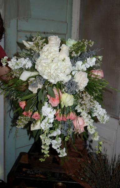 This bridal bouquet was designed with white cala lilies, white hydrangeas, white roses, peach roses, light mint roses, white larkspur with a touch of grey misty & mixed greens.