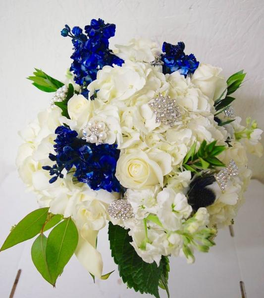 [Image: This bridal bouquet is designed with white hydrangea, white roses, white & navy stock, pearl & bling brooches with myrtle & seeded etc. The stems were wrapped in white satin ribbon with navy blue overlay. ]