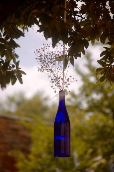 [Image: We used royal blue wine bottles filled with baby's breath & trimmed with a sheer white ribbon. The ribbons were hanging from the tree limbs to give the wedding that added touch that tied in all of the decor in a romantic feel.]