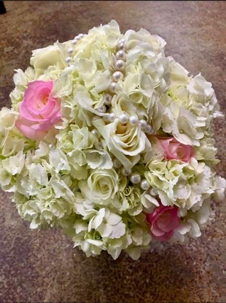 [Image: This bridal bouquet is designed with white hydrangeas, white roses, pink roses & pearls wrapped through the bouquet and down the stems.]